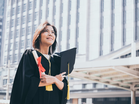 Graduation day, Asian woman with graduation cap and gown holding diploma, Successful concept Stock Photo