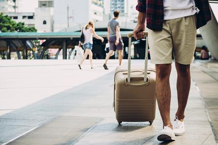 街の通りで荷物を持って旅行者をクローズアップ。休暇と旅行のコンセプト
