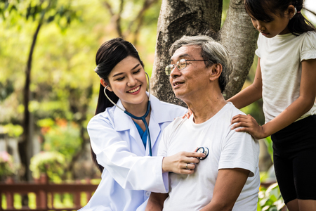 Young female doctor using the stethoscope listen to elderly patient heartbeat in hospital garden Stockfoto
