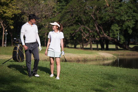 Asian young couple playing golf on golf course, the male partner is trainer to the female golfer Banco de Imagens