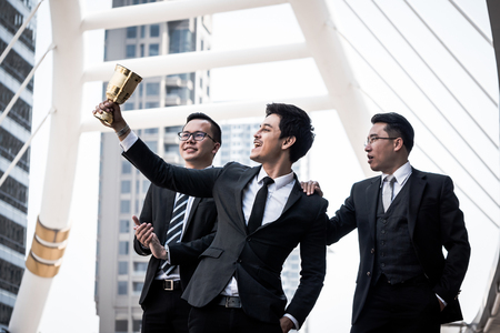 Happy Asian business people with golden trophy cup for their winner in business project. Teamwork  and success concept