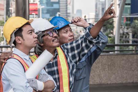 Architect, civil engineer and worker at construction site working together on buildings blueprint. Teamwork concept
