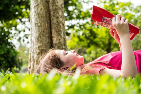 Beautiful girl reading a book on green grass in a park