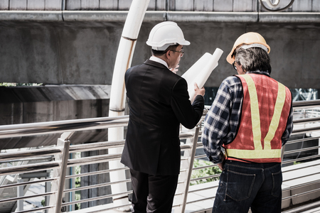 Business man holding buildings blueprint and talking discussing with architect working at at construction site.
