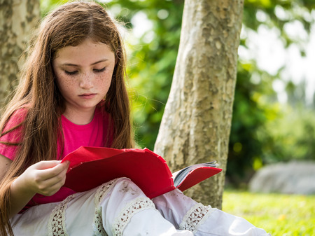 Beautiful girl reading a book while sitting on green grass in a park Stockfoto