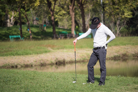 Frustrated golf player standing on the golf course.