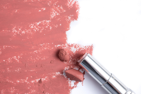 Smudged pink lipstick on white background.