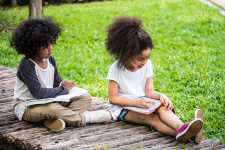 Little boy and girl reading  book while sitting on ground in a park.