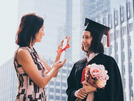 Beautiful woman congratulates for her daughter on graduation day, Successful concept Banco de Imagens