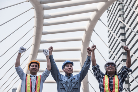 Architect, civil engineer and worker raising arms up together for success with construction site background. Teamwork concept. Stock Photo