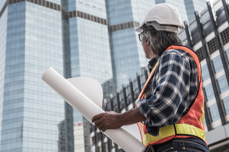Architect or civil engineer holding buildings blueprint with construction site background.