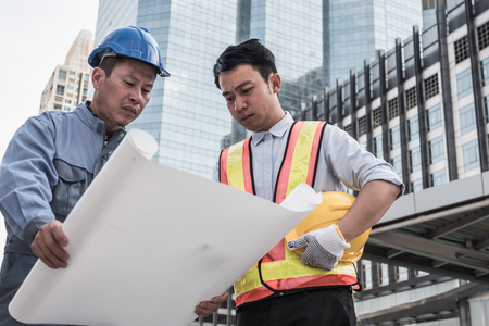 Architect and civil engineer at construction site working together on buildings blueprint. Teamwork concept Stock Photo
