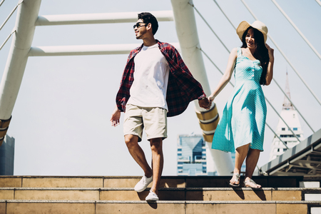 Couple Asian travelers are walking and enjoying vacations on city street. Travel concept 写真素材