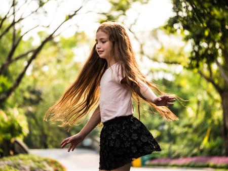 A little girl having fun dancing in a park. Stock Photo