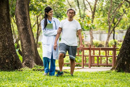 Jonge vrouwelijke arts die aan hogere patiënt in het ziekenhuistuin spreekt