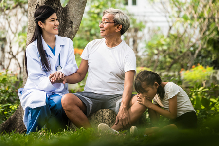 Young female doctor talking to senior patient with granddaughter in hospital garden