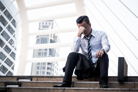 Frustrated Asian young business man sitting in front of the office building.