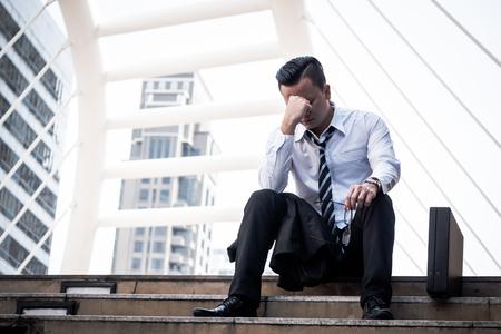 Giovane uomo asiatico frustrato di affari che si siede davanti all'edificio per uffici. Archivio Fotografico