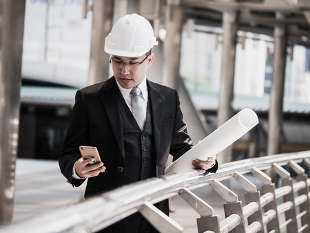 Construction engineering consultant holding buildings blueprint and using smart phone at construction site.