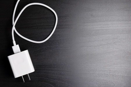 White electric plug cable on black wooden table background. copy space