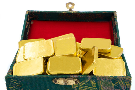 Close up of Pure gold bars in green box on white background.
