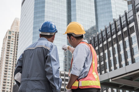 Back view of Architect and civil engineer at construction site working together. Teamwork concept