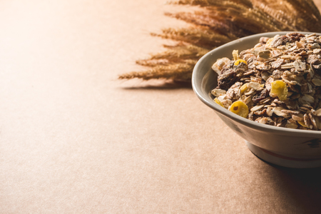 Oatmeal flakes in a bowl on wooden table. Healthy breakfast concept. copy space Imagens