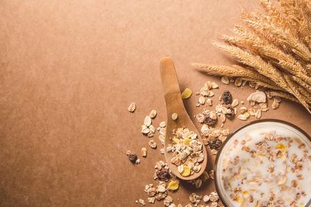 木製のテーブルの上にシリアルとミルクのカップ。健康的な朝食のコンセプト。スペースをコピーします。トップ ビュー