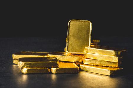 Stapel von reinen Goldbarren auf schwarzem Hintergrund Standard-Bild