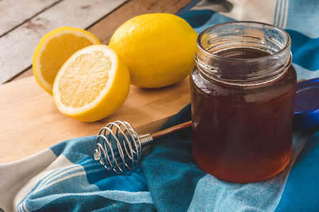 A glass of honey with dipper and lemon on the table.