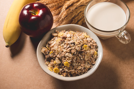 Oatmeal flakes in a bowl, milk, apple and banana on wooden table. Healthy breakfast concept. Imagens