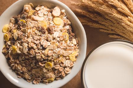 ボウルのオートミールフレークと木製テーブルの上のミルクのトップビュー。健康的な朝食のコンセプト。