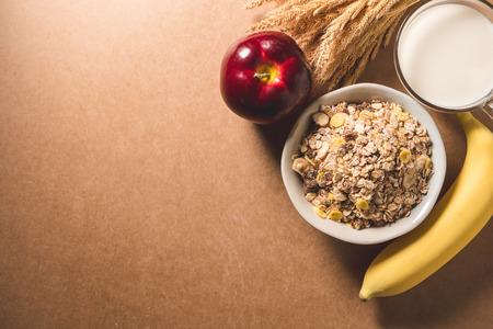 ボウル、ミルク、リンゴ、バナナのオートミールフレーク。健康的な朝食のコンセプト。スペースのコピー