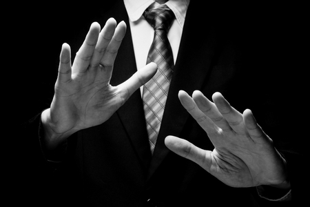 Close up of man in black suit with hand gesture on black background. black and white tone
