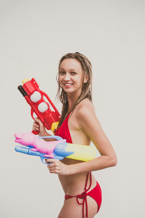 Attractive young woman in the red bikini holding water guns on white background Stock Photo
