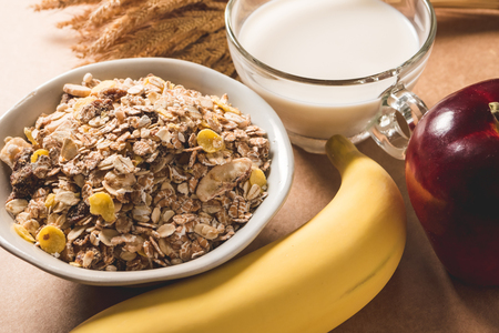 Oatmeal flakes in a bowl, milk, apple and banana on wooden table. Healthy breakfast concept. Imagens - 99485876