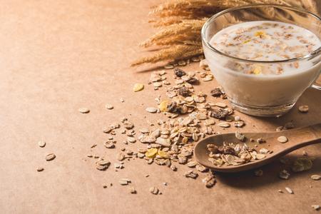 木製のテーブルの上にシリアルとミルクのカップ。健康的な朝食のコンセプト。スペースをコピーします。