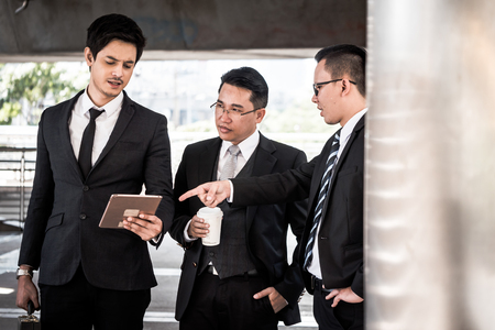 Asian business people talking together with stress feeling while standing in front of the office building.