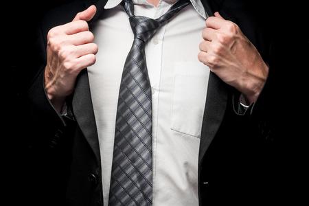 Close up of businessman taking off his suit on black background Banco de Imagens