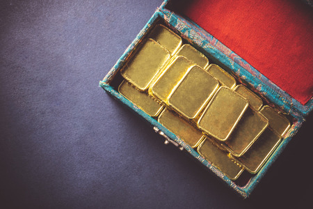 Top view of Pure gold bars in the box on dark background. copy space