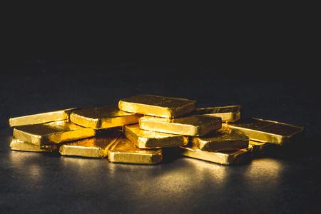 Stapel von reinen Goldbarren auf schwarzem Hintergrund