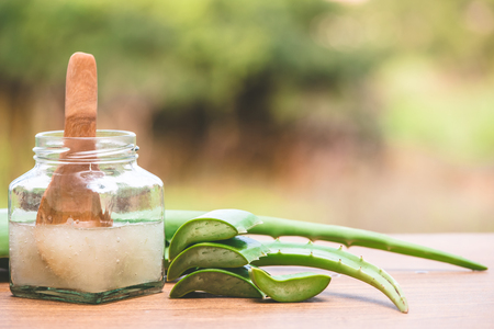 Fresh aloe vera and jelly in glass bottle on wooden table with nature background