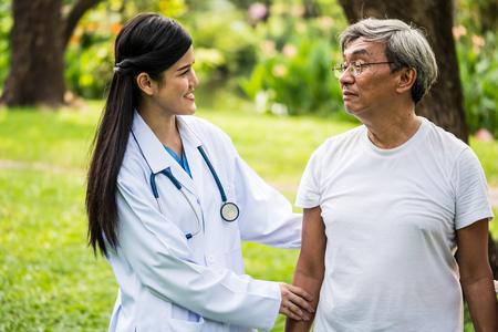 Jonge vrouwelijke arts die aan hogere patiënt in het ziekenhuistuin spreekt Stockfoto