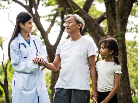 Jonge vrouwelijke arts die aan hogere patiënt met kleindochter in het ziekenhuistuin spreekt