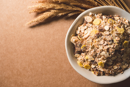 Top view of oatmeal flakes in a bowl on wooden table. Healthy breakfast concept. copy space