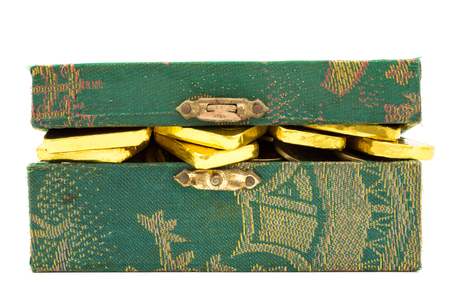 Pure gold bars and coins in green box on white background. Banco de Imagens