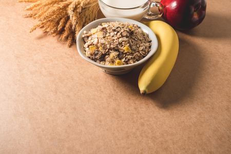 Oatmeal flakes in a bowl, milk, apple and banana on wooden table. Healthy breakfast concept. copy space