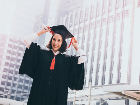 Graduation day, Young woman with graduation cap and gown holding diploma, Successful concept Stock Photo