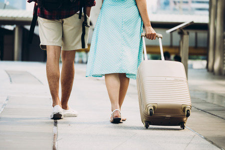 Close up of Couple travelers with luggage wakling on city street. Vacation and travel concept