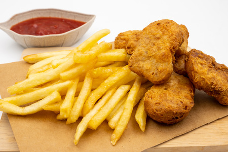 Close up of French fries with nuggets and ketchup on a white background.